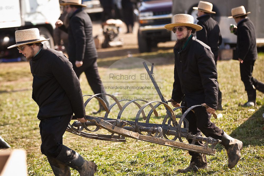 Amish men carry home purchases following the Annual Mud Sale to support the Fire Department in Gordonville, PA.