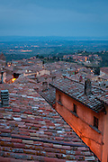 View across the rooftops of Montepulciano at dusk, with Lake Trasimeno visible in the distance, Siena, Tuscany, Italy.