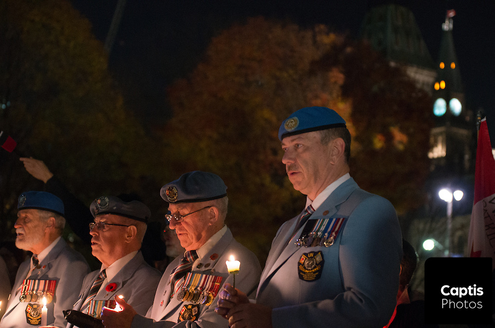 The Peace Tower on Parliament Hill is seen behind veterans holding candles during a vigil for Cpl. Nathan Cirillo. October 25, 2014.
