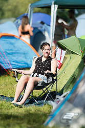 © Licensed to London News Pictures. 13/06/2014. Isle of Wight, UK.   A girl relaxes in the early morning sun beside her tent  at Isle of Wight Festival 2014 - today is expected to be the hottest day of the year in the UK.   The Isle of Wight festival is an annual music festival that takes place on the Isle of Wight. Photo credit : Richard Isaac/LNP