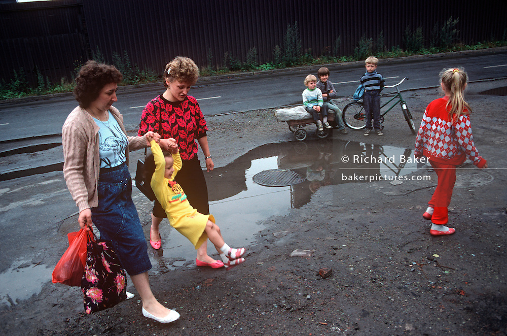 Mothers swing a child across a filthy puddle in the town of Nova Huta, an industrial Stalinist steel town oin southern Poland..In filthy industrial streets, the kids look undernourished in this scene of impoverished, Communist dereliction. It is horribly depressing and unhealthy place to grow up and these children are pale and yet seem happy, with smiles on their faces. The famous steel works can be seen reflected in the puddle before them. After the war, Stalin decided to build an industrial Communist fantasy just outside Krakow: a model town and immense steelworks of the future. The steelworks was named after Lenin and the town would be called Nowa Huta  - or, the new steel mill. At its peak, 27,000 people worked at the Lenin Steelworks. But Solidarity grew strong forcing strikes over pay and recognition over their union. Today, it is an economic and ecological disaster area.