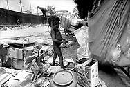 A naked homeless child is playing alone in a mess of rubbish things, Phnom Penh, Cambodia, Asia.