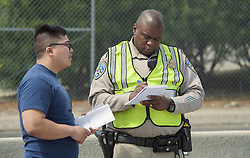June 30, 2017 - Irvine, CA, USA - Witness Neilson Dong talks with a California Highway Patrol officer after a small plane crashes misses the runway at John Wayne Airport and crashes on I-405 freeway at MacArthur in Irvine, CA, injuries are unknown on Friday, June 30, 2017. (Credit Image: © Ken Steinhardt/The Orange County Register via ZUMA Wire)