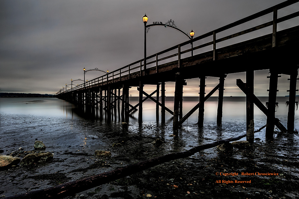 Leading Lines: Sunrise and the eye is drawn down two tangential lines made of the log and a wooden pier, White Rock, Surrey British Columbia Canada.
