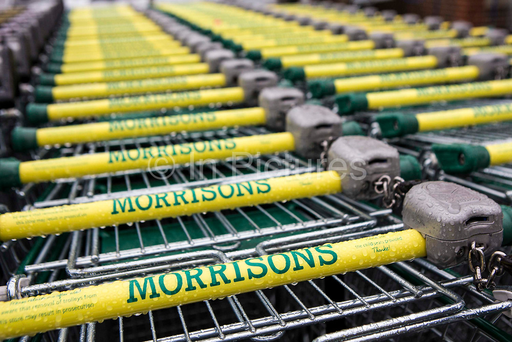 A long line of Morrisons supermarket shopping trolleys parked outside the shop in the rain in Blandford Forum, United Kingdom.  Wm Morrison Supermarkets is the fourth largest chain of supermarkets in the United Kingdom.