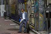 A salaryman checks his smart phone in a graffiti-covered alleyway in Shibuya, Tokyo, Japan. Tuesday June 23rd 2020