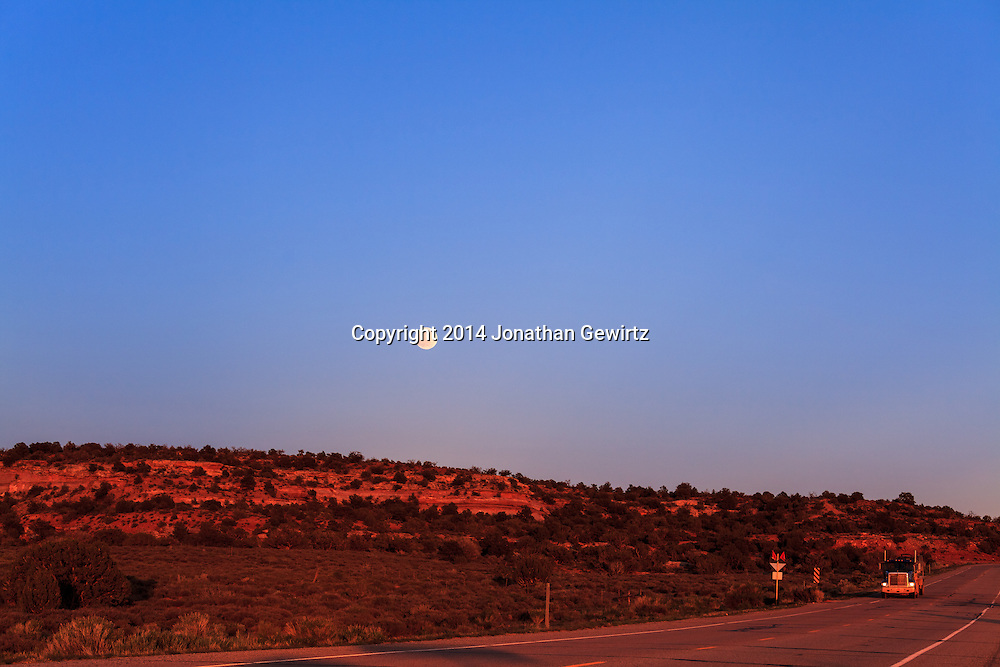 The full moon rises over desert hills glowing red in the last rays of the setting sun, adjacent to Utah Highway 313 on the high plateau northwest of Moab.<br /> WATERMARKS WILL NOT APPEAR ON PRINTS OR LICENSED IMAGES.