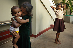 Shrianna Barthelot, 11, comforts her newborn nephew Dean Ragel while friend Selsiya Stockraz, 13, looks on, Batticaloa, Sri Lanka, Jan. 28, 2005. Shrianna and her sister Brianna, 13, not pictured here, lost both parents and their older brother in the tsunami. They are now living with relatives at night and spending most of their days at the convent where the rest of their village is staying. Residents of the small Christian village Dutch Bar spent more than six weeks in a makeshift refugee camp at the local convent recovering from the devastating tsunami that hit the eastern and southern borders of Sri Lanka. They were then moved into another temporary living camp, while awaiting the building of new homes. More than 150 members in this community of less than 1000 people died in the tragic event.