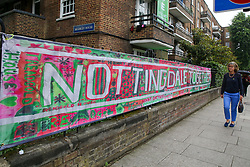 © Licensed to London News Pictures. 14/06/2019. London, UK. A woman walks past a large message left on railings to commemorate the second anniversary of the Grenfell Tower fire service. On 14 June 2017, just before 1:00 am a fire broke out in the kitchen of the fourth floor flat at the 24-storey residential tower block in North Kensington, West London, which took the lives of 72 people. More than 70 others were injured and 223 people escaped. Photo credit: Dinendra Haria/LNP