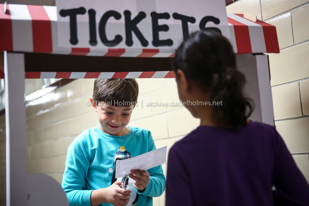"""(12/21/15, MILFORD, MA) First-grader Pedro Souza-Rodrigues punches tickets for the showing of the """"Polar Express"""" at Milford Catholic Elementary School on Monday. Daily News and Wicked Local Photo/Dan Holmes"""
