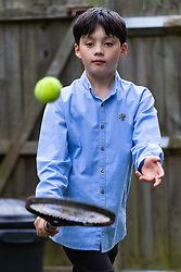 Reuben, 11, playing tennis in the garden with his brother. Brothers Reuben and Josh Moisey are top level Scrabble Champions with 11 year-old Reuben crowned European Youth Scrabble Champion and 8 year-old Josh became World Under Eight Scrabble Champion in Dubai in 2018. London, August 15 2019.