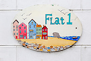 Seaside scene painted on flat sign in Aldeburgh, Suffolk, England, UK