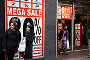 Women outside the Mega Sale on Oxford Street, London. A massive 80 percent is marked off many items.
