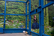 Scissor lift and model in a fantasy garden printed on temporary construction hoarding poster at a Dior shop being refurbished On Bond Street, central London. The blue struts and bars of the safety cage frame the model seen on the background. The Dior store occupies a prime location on one of London's most prestigious streets known for fashion and jewellery and work continues behind the screen, hidden to passers-by.