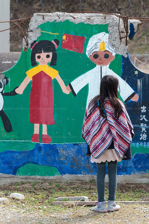 A young girl visits Okawa Elementary school in Ishinomaki, Miyagi, Japan. Thursday March 10th 2016. The Great East Japan Earthquake struck at 2:46pm on March 11th 2011 levelling much of the Tohoku coast and causing the deaths of around 18,000 people. including 84 students and staff at Okawa Elementary School.