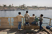 Schoolboys stand on the top deck of the state-run ferry across the River Nile at Luxor, Nile Valley, Egypt.