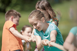 Group of children playing tug-of-war in a park, Munich, Bavaria, Germany