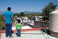 Dal tetto della casa di sua madre, dove sono stati costretti a trasferirsi, Simon e suo figlio guardano la casa che è stata loro portata via.
