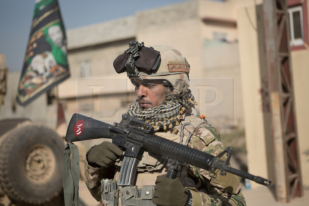 Licensed to London News Pictures. 11/11/2016. Mosul, Iraq. A soldier, belonging to the Iraqi Army's 9th Armoured Division, stands guard as his unit visits Mosul's Al Inisar district on the south east of the city. The Al Intisar district was taken four days ago by Iraqi Security Forces (ISF) and, despite its proximity to ongoing fighting between ISF and ISIS militants, many residents still live in the settlement without regular power and water and with dwindling food supplies.<br /> <br /> The battle to retake Mosul, which fell June 2014, started on the 16th of October 2016 with Iraqi Security Forces eventually reaching the city on the 1st of November. Since then elements of the Iraq Army and Police have succeeded in pushing into the city and retaking several neighbourhoods allowing civilians living there to be evacuated - though many more remain trapped within Mosul.  Photo credit: Matt Cetti-Roberts/LNP