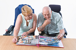 Disabled couple looking through a photo album together,
