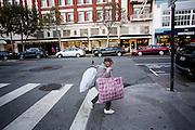 Een zwerver loopt met verzameld plastic door Polk Street in San Francisco. De Amerikaanse stad San Francisco aan de westkust is een van de grootste steden in Amerika en kenmerkt zich door de steile heuvels in de stad.<br /> <br /> A homeless woman walks with collected plastic garbage at Polk Street in San Francisco. The US city of San Francisco on the west coast is one of the largest cities in America and is characterized by the steep hills in the city.
