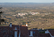View over rooftops to lowland below and towards the hills and the border with Spain. The village of Santo António das Areias with its whitewashed buildings is in the centre of this scene. Photo taken from Marvao, Portalegre district, Alto Alentejo, Portugal, Southern Europe