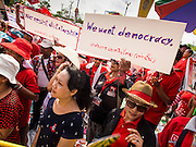 06 APRIL 2014 - BANGKOK, THAILAND: Red Shirts supporters at a pro government rally hold up signs protesting the Thai courts and military who they suspect of harboring anti-government factions. Red Shirts and supporters of the government of Yingluck Shinawatra, the Prime Minister of Thailand, gathered in a suburb of Bangkok this weekend to show support for the government. The Thai government is dealing with ongoing protests led by anti-government activists. Legal challenges filed by critics of the government could bring the government down as soon as the end of April. The Red Shirt rally this weekend was to show support for the government, which public opinion polls show still has the support of most of the electorate.   PHOTO BY JACK KURTZ
