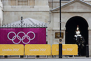 The Olympic rings on a banner outside Horse Guards where a soldier from the Household Cavalry sits motionless on his horse during the London 2012 Olympics. Wrought iron railings are seen behind the banner at the sports venue hosting the volleyball in the centre of Westminster where governmental offices are located. The British Household Cavalry is classed as a corps in its own right, and consists of two regiments: Life Guards (British Army) and the Blues and Royals (Royal Horse Guards and 1st Dragoons). They are the senior regular regiments in the British Army, with traditions dating from 1660.