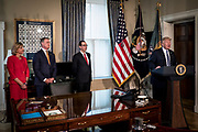 Rep. Claudia Tenney, R-N.Y., Sen. David Perdue, R-Ga., and Treasury Secretary Steven Mnuchin look in as President Donald Trump delivers remarks before the signing of one executive order and two presidential memoranda on tax and Wall Street regulations in Washington, District of Columbia, U.S., on Friday, April 21, 2017. This was President Trump's first visit to the Treasury Department.