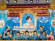 09 AUGUST 2015 - BANGKOK, THAILAND:  Women carry a portrait of Queen Sirikit of Thailand across the stage during a talent show in Bangkok to honor the Queen before her birthday. Sirikit was born Mom Rajawongse Sirikit Kitiyakara on 12 August 1932, is the queen consort of Bhumibol Adulyadej, King (Rama IX) of Thailand. She met Bhumibol in Paris, where her father was the Thai ambassador. They married in 1950, shortly before Bhumibol's coronation. Sirikit was appointed Queen Regent in 1956. Sirikit produced one son and three daughters. As the consort of the king who is the world's longest-reigning head of state, she is also the world's longest-serving consort of a monarch. Sirikit suffered a stroke on 21 July 2012 and has since refrained from public appearances. Her birthday is celebrated as Mother's Day in Thailand.     PHOTO BY JACK KURTZ
