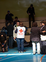 Chile Red Cross Worker in the E 3 School Auditorium. Red Cross Refuge Center, Puerto Natales E3 School. Snapshot taken with a Leica D-Lux 5 camera (ISO 80, 19.2 mm, f/3.3, 1/125 sec).