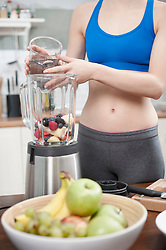 Young woman making smoothie with fruits in the kitchen, Bavaria, Germany