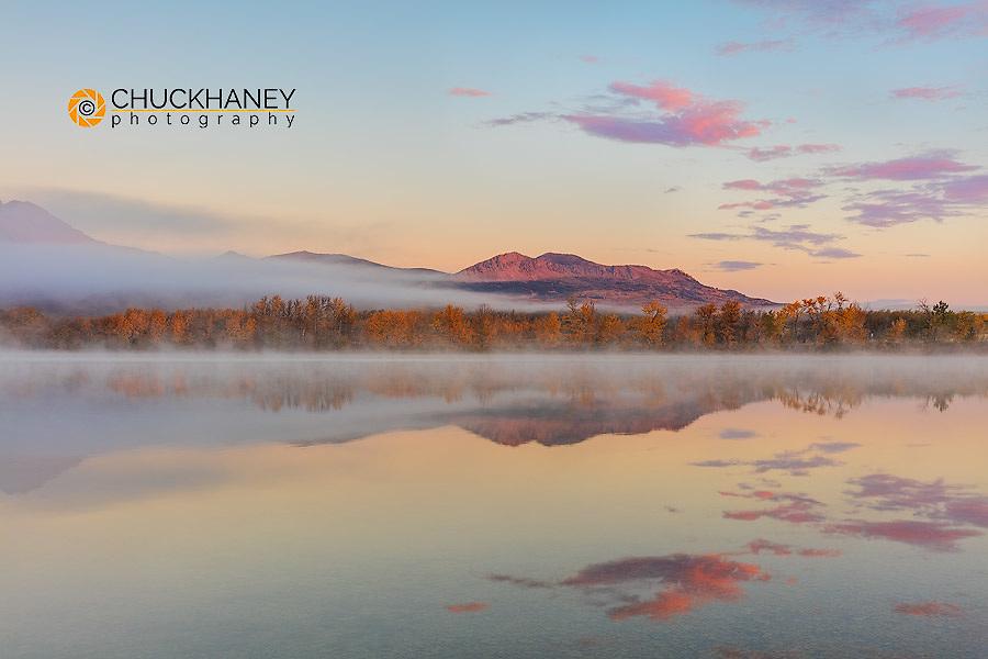Sunrise clouds and Lakeview Ridge reflect into Maskinonge Lake in Waterton Lakes National Park, Alberta, Canada