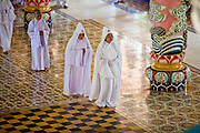 "10 MARCH 2006 - TAY NINH, VIETNAM: Priests and congregants file into the Cao Dai temple in Tay Ninh before noon prayers. The Cao Dai complex in Tay Ninh is the sect's headquarters. The Cao Dai religion is a blending of Buddhism, Confucianism, Taoism, Christianity and Islam. There ""saints""  include Chinese leader Sun Yat Sen and French author Victor Hugo. There are about two million members of the Cao Dai religion in Vietnam. British author Graham Greene, who wrote about the Cao Dai in the ""The Quiet American"" said the relegion was ""a Walt Disney fantasia of the East."" The Cao Dai hold services four times a day: midnight, 6AM, noon and 6PM. Photo by Jack Kurtz / ZUMA Press"