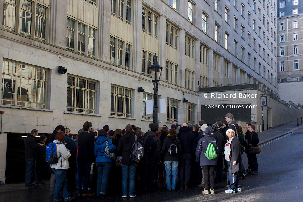 A tour group organised by WalkLondon stop to hear about London's still working gaslight outside the Savoy Hotel in Carting Lane WC2 - and said to be powered by sewer gas.
