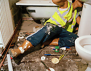 Plumber Pauline Brown in a flat conversion..Pauline Brown lies across the floor in a converted Hackney council flat bathroom.