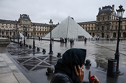 December 14, 2017 - Paris, Ile-de-France, France - Woman is seen walkign past the Louvre museum in Paris, France. People and tourists dont afraid for take a walk and taking pictures around the Paris landmarks althought the cold and rainy weather above the French capital, Paris, France on December 15, 2017  (Credit Image: © Hristo Rusev/NurPhoto via ZUMA Press)