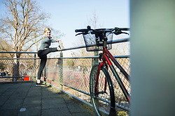 Woman in sportswear stretching on bridge with bicycle in foreground