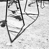 Children on a swing..Families moods go up and down. The lack of hope and the constant reference to the past weigh heavily on the children...During the summer1999, over 245,000 Serbs and Roms fled to Serbia and Montenegro from or within Kosovo in fear of reprisals from the majority Albanian population, after NATO air strikes had forced the withdrawal of Yugoslav. In 2003, less than 2% of them had returned and a large number of these internally displaced persons (IDPs) were still living in camps in very difficult conditions..In addition, around 5,000 IDPs, mainly of Roma ethnicity, are living in unrecognized collective centres, makeshift huts, corrugated metal containers and other substandard shelters. .This work was meant to look at how the life of children and young adults is affected by the fact that they are IDPs. I asked myself more specifically what would be different for these children/young adults from the 'normal' people of their age as far as education, health, social life, family, 'love' life and leisure are concerned. ..Enfants sur des balançoires..L'ambiance dans les familles est souvent à l'image du mouvement de ces balançoires. Le manque d'espoir et les références constantes faites au passé pèsent très fortement sur les enfants....Pendant l'été 1999, plus de 245 000 serbes et roms ont fuit le Kosovo pour chercher refuge en Serbie ou au Montenegro, par peur de représailles de la part de la majorité de la population albanaise après que les forces de l'OTAN aient forcé l'armée yougoslave à se retirer. En 2003, moins de 2% d'entre eux étaient rentrés chez eux et le plus grand nombre de ces 'déplacés' (IDPs) vivaient encore dans des centres d'accueil dans des conditions très difficiles..Environ 5 000 IDPs, la plupart romas, vivent dans des centres non reconnus faits de containers ou d'abris de fortune. .Ce travail s'est focalisé sur les jeunes IDPs, sur les conséquences de leur état de 'déplacés' sur leur vie et plus particulièrement dans les sphères concern