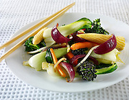 Oriental vegetarian stir fry being lifted  by chop sticks in a table setting with rice & a chilli dipping sauce