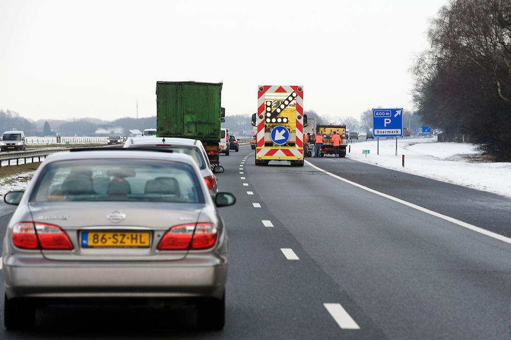 Nederland, Apeldoorn, 3 feb 2010..Wegwerkzaamheden wegens vorstschade aan zoab asfalt. Door bevriezing vallen er veel gaten in de weg. Dat zorgt voor veel opspattend grind. Automobilisten zouden langzamer moeten rijden om schade aan autoruiten te voorkomen...Foto (c) Michiel Wijnbergh..