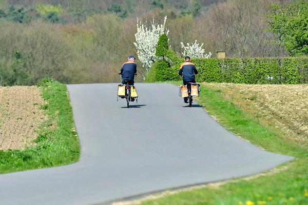 Nederland, 18-4-2018Twee postbezorgers rijden, fietsen naast elkaar buiten het dorp .Foto: Flip Franssen