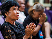 26 OCTOBER 2017 - BANGKOK, THAILAND:  Women pray while they watch the televised broadcast of the royal funeral in the waiting area of Hua Lamphong train station during the funeral ceremony for Bhumibol Adulyadej, the Late King of Thailand. The king died on 13 October 2016 and was cremated 26 October 2017, after a mourning period of just over one year. The revered monarch was the longest reigning king in Thai history and is credited with guiding Thailand through the turbulent latter half of the 20th century.  PHOTO BY JACK KURTZ