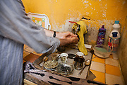 Delal's husband washes his hands in their kitchen zink. Delal walks along the narrow alleys to her temporary home in Shatila. She is a Palestinian from Damascus and now lives as a refugee in Shatila, a Palestinain camp in Beirut. She lives in Shatila with her extended family after they had to flee the war in Syria.