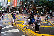 A mother and daughter cross a busy road crossing in the Causeway Bay area of Hong Kong, China. The little girl wears a face mask to protect her from the polluted air. Causeway Bay is a thronging shopping district, with a slightly less western influence than nearby Central district.