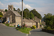 The village church in Muker in Swaledale, which runs broadly from west to east. To the south and east of the ridge a number of smaller dales. Swaledale is a typical limestone Yorkshire dale, with its narrow valley-bottom road. Yorkshire, England, UK.