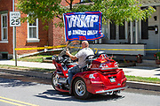 A man on a three-wheeled motorcycle waves Trump flag as he drives on Chestnut Street during the Mifflinburg Pride Event.