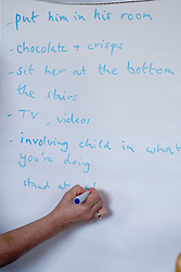 A  teacher writing on a  flipchart in a parenting class; run by the Aspire Training Scheme for young mothers and mothers to be,