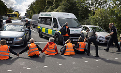 © Licensed to London News Pictures. 29/09/2021. Swanley, UK. Police and motorists clear Insulate Britain activists to allow the passage of an ambulance as they block the road near to junction 3 of the M25 motorway near Swanley for the second time today. 11 members of the campaign group were detained at the same junction earlier today. This is the seventh time in just over two weeks that activists have disrupted traffic on London's orbital motorway despite the government being granted a temporary High Court Injucntion banning the group from protesting on the M25. 50 protesters who were detained after Monday's protest, on junction 14 of the M25 at Heathrow, were released. Photo credit: Peter Macdiarmid/LNP
