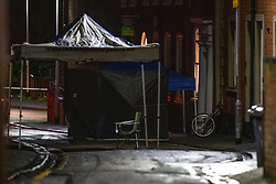 © Licensed to London News Pictures. 19/01/2021. Reading, UK. Police tents and a bicycle on Church Street in Reading at the scene where a man was stabbed. At approximately 20:15GMT on Monday 18/01/2021 in Church Street, Reading, a man in his forties was assaulted by a group of unknown offenders with weapons who fled the scene after the assault. The victim was taken to hospital with injuries consistent with having been stabbed. Photo credit: Peter Manning/LNP